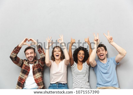Photo of happy group of friends sitting isolated over grey wall background gesturing with hands.