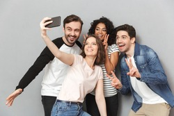 Photo of happy group of friends standing isolated over grey wall background looking aside make a selfie.