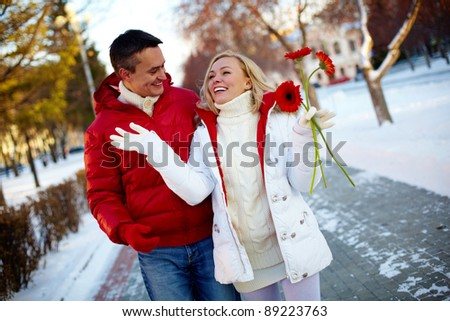 Photo of happy man and pretty woman walking outdoor in winter