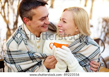 Photo of happy man and pretty woman with cups outdoor in winter