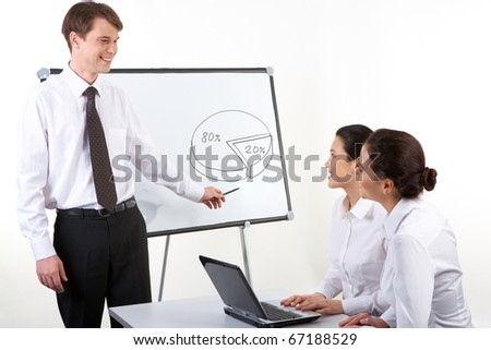 Photo of happy man commenting diagram to his colleagues who sitting at the desk and looking at him