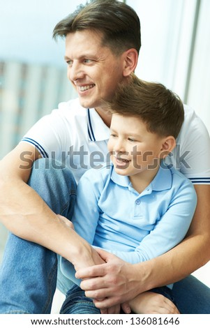 Photo of happy man embracing his son