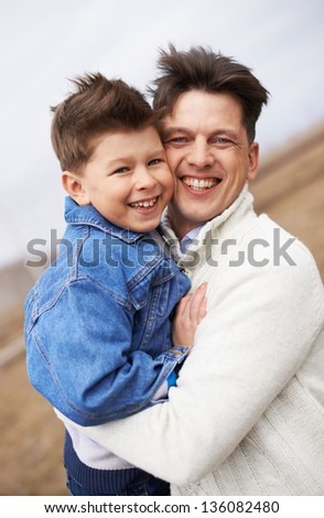 Photo of happy man embracing his son and both looking at camera