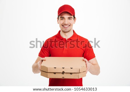 Photo of happy man from delivery service in red t-shirt and cap giving food order and holding two pizza boxes isolated over white background