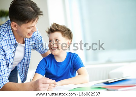 Photo of happy man looking at his son while talking to him at home