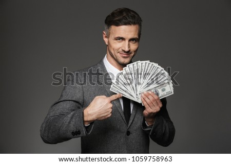 Photo of happy man 30s in formal costume demonstrating lots of money dollar banknotes and pointing finger on bills isolated over gray background #1059758963
