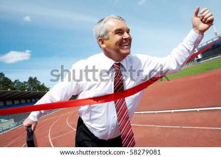 Photo of happy mature businessman crossing finish line during race - stock photo