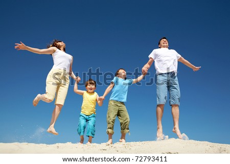 Photo of happy parents holding their son by hands in jump with bright blue sky at background