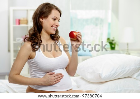 Photo of happy pregnant woman holding ripe apple