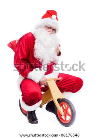 Photo of happy Santa Claus on bike with red sack. Isolated over white background