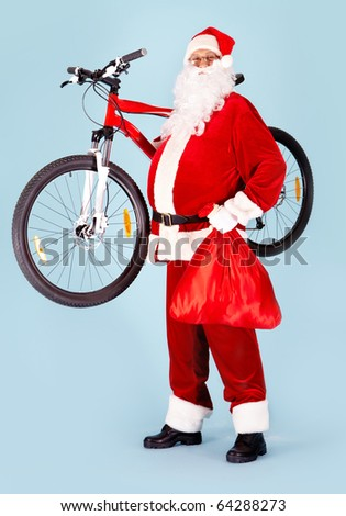 Photo of happy Santa Claus with red sack and bike looking at camera