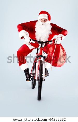Photo of happy Santa Claus with red sack on bike