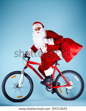 Photo of happy Santa Claus with red sack riding bike
