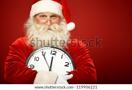 Photo of happy Santa holding clock showing five minutes to midnight