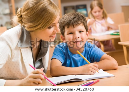 Photo of happy schoolboy looking at camera with teacher near by