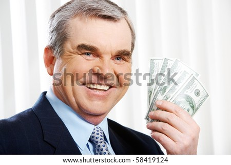 Photo of happy senior businessman showing dollar banknotes