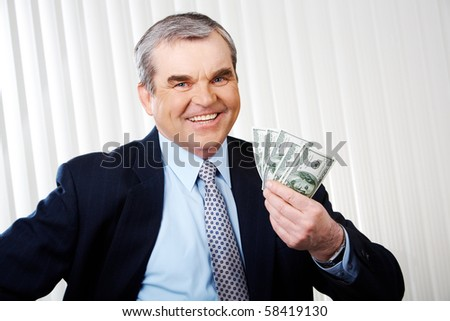 Photo of happy senior businessman with dollar banknotes