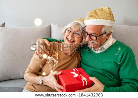 Photo of  Photo of Happy senior couple exchanging Christmas presents during the day at home. Elderly woman giving present to her beloved husband. Gray hair couple celebrating New Year