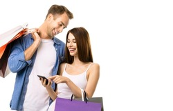 Photo of happy smiling couple with shopping bags, and phone, standing close to each other. Love, holiday sales, shop, retail, discounts, rebates deals consumer concept, isolated on white background.