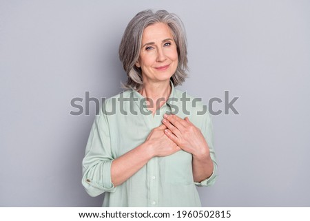 Photo of happy smiling dreamy lovely granny hold hands chest thankful grateful isolated on grey color background