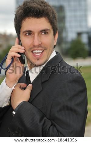 Photo of happy winner businessman  talking on mobile phone - stock photo