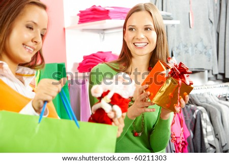Photo of happy woman looking at her friend with paperbag choosing gifts in trade center