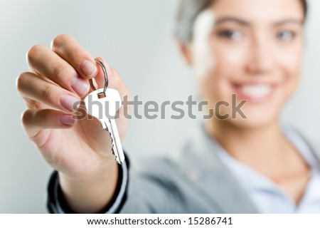 Photo of happy womanâ??s hand holding new key and pointing it at camera