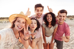 Photo of happy young multiracial people in summer clothes taking selfie while standing at the beach during sunset