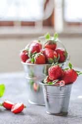 Photo of heap of fresh strawberries in the bowl on rustic grey background.A bunch of ripe strawberries in a can bowl on the table. Copy space. Healthy fresh fruit. Organic food. Clear food