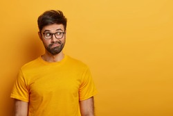 Photo of hesitant bearded man looks aside, smirks face and has puzzled expression, tries to decide something, dressed in casual yellow t shirt, poses over vibrant studio wall, wonders what he sees