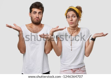Photo of hesitant boyfriend and girlfriend look with uncertainty, recieve suggestion, have doubtful facial expressions, wears white t shirt in one tone with background. Who cares, we dont know