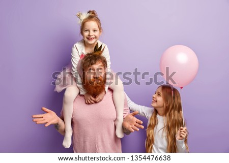 Photo of hesitant dad spreads hands, has conversation with daughters, asks what to present, spend free time together, prepare for holiday celebration, go on birthday, pose over lilac background