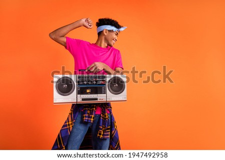 Photo of hipster guy hold boombox dance wear pink t-shirt plaid knotted shirt headband isolated orange background Stockfoto ©