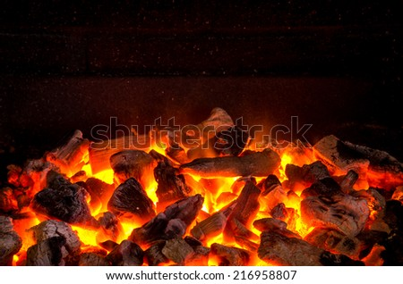Photo of hot sparking live-coals burning in a barbecue  #216958807