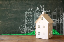 photo of house and background of blackboard and city drawings. real estate and family house concept
