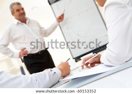 Photo of human hands over workplace on background of senior boss explaining his idea by the board