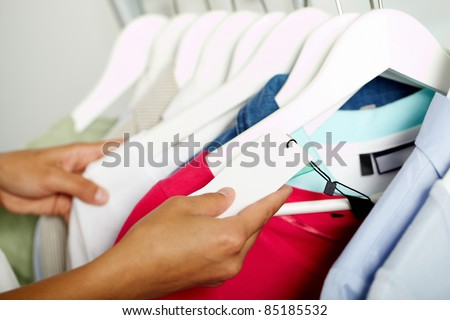 Photo of human hands searching through hangers with clothes