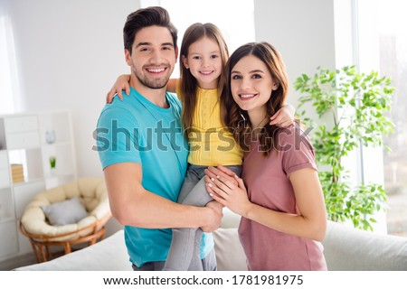 Photo of idyllic three people mommy daddy carry small kid daughter enjoy gentle bonding emotions hug embrace in house indoors