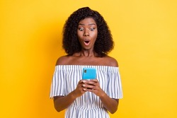 Photo of impressed dark skin girl open mouth staring phone unexpected bad fake news isolated on yellow color background