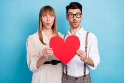 Photo of impressed funny two persons dressed white clothes holding big paper heart isolated blue color background