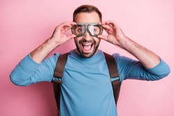 Photo of impressed young man dressed blue sweater arms eyewear rucksack ready jump parachute isolated pink color background