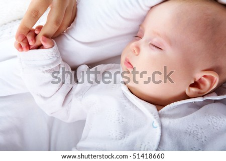 Photo of innocent baby sleeping in cradle and mother touching him
