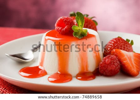 photo of italian panna cotta dessert with strawberry sirup and mint leaf