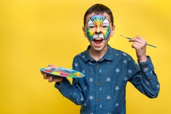 Photo of ittle cute boy with faceart on birthday party, cute colorful tiger holding palette with gouache isolated on yellow background.