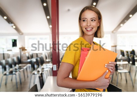 Photo of joyful blonde woman holding exercise books and smiling while standing in open-plan office