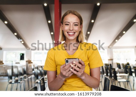 Photo of joyful blonde woman using cellphone and smiling while leaning on table in open-plan office