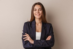 Photo of joyful businesswoman in formal suit smiling at camera with arms crossed isolated over white background