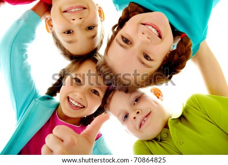 Photo of joyful children touching by their heads with girl her thumb up - stock photo