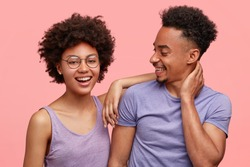 Photo of joyful dark skinned female and male companions have joy together, dressed casually, smile positively, stand against pink background. Happy African American woman leans at shoulder of man