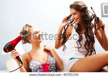 Photo of joyful females taking care of their hair while chatting